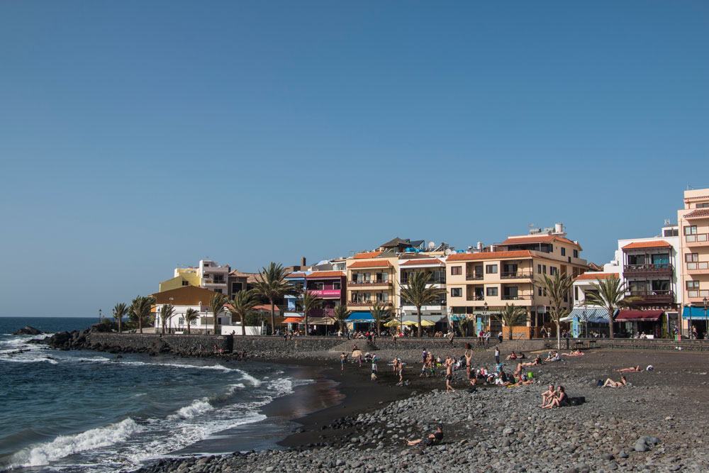 The black sandy beach of La Calera with colored houses