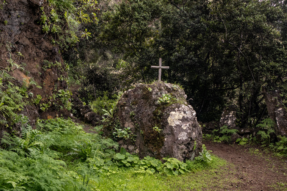 Stone with cross at the hiking path