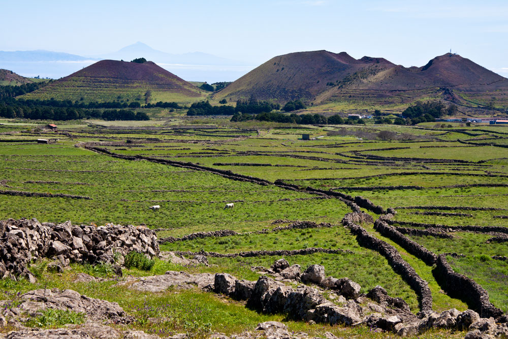 green plateau with stone walls and hiking trails