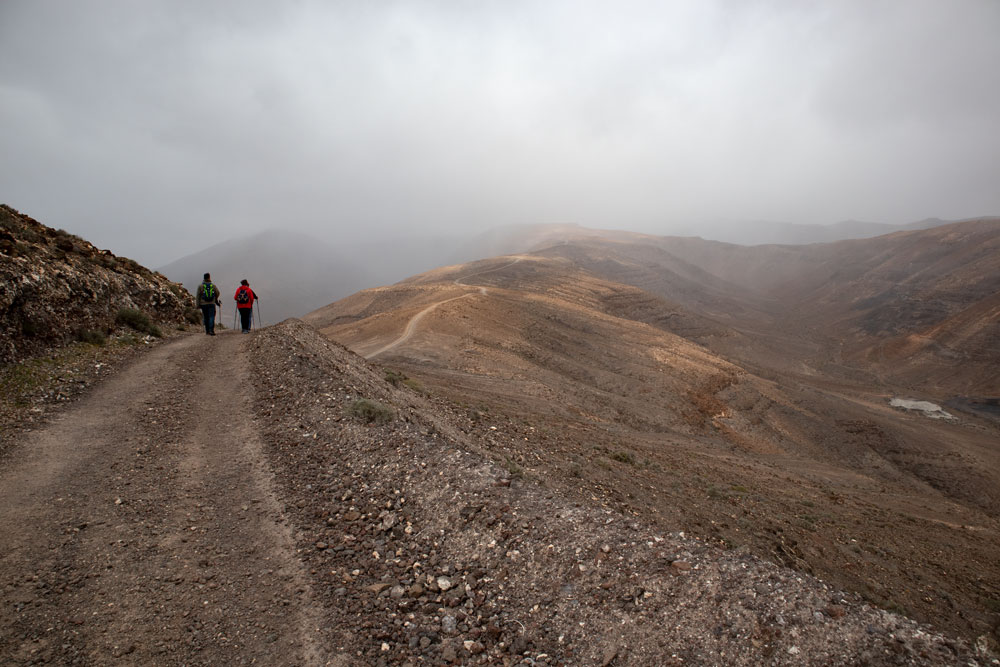 hikers on the wide hiking path over the ridge in clouds