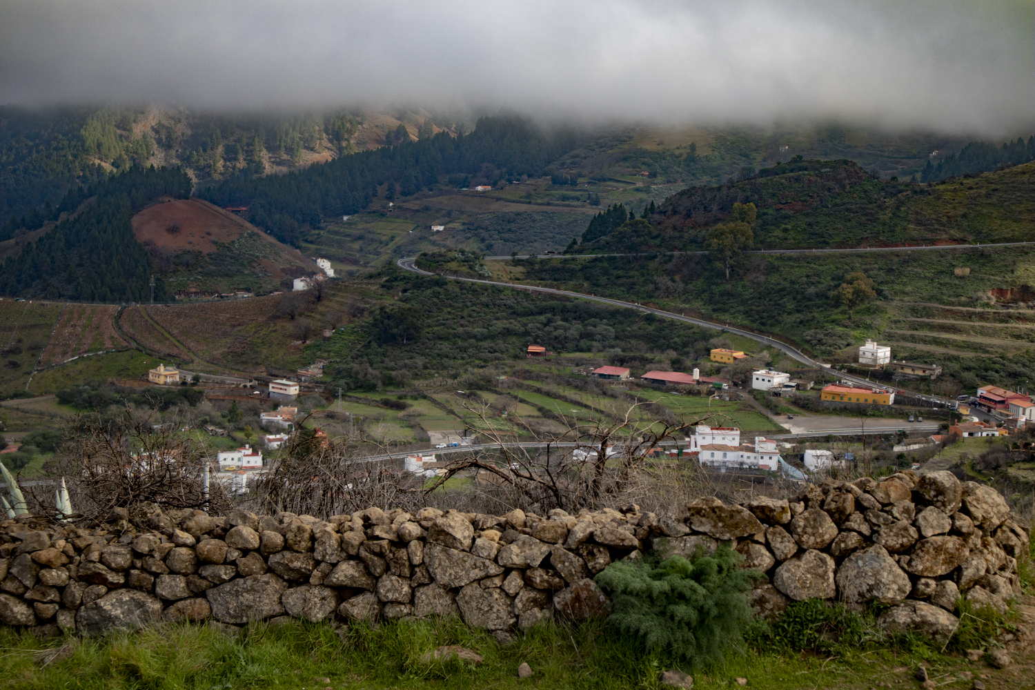 View of the hamlet of Cueva Grande from the viewing plateau behind the stone wall